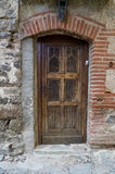 Old brown door of a morbid house. In Eus, France Stock Images