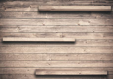 Old brown empty shelf on wooden wall Stock Images