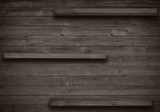 Old brown empty shelf on wooden wall Royalty Free Stock Images