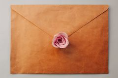 an old brown envelope, pink rose flower on a blue background. Minimal Flat lay stock image