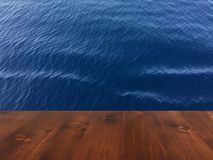 Old brown oak wooden deck table on the blue sea background, wood table.  royalty free stock photo