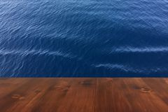 Old brown oak wooden deck table on the blue sea background, wood table. Abstract royalty free stock images