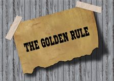 Old brown paper with THE GOLDEN RULE text on wooden background. Royalty Free Stock Images