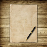 Old brown paper and pen on wooden wall background for texture Stock Photography