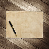 Old brown paper and pen on wooden wall background for texture Stock Images