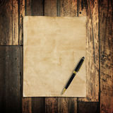 Old brown paper and pen on wooden Royalty Free Stock Photos