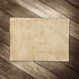 Old brown paper on wooden wall background for texture.  Royalty Free Stock Image