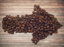 Old brown planks and coffee beans arrow. Collage Stock Photos