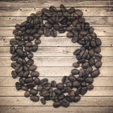 Old brown planks and coffee beans circle. Collage Royalty Free Stock Images