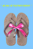 Old brown sandals on isolate blue background. Old sandals on isolate blue background. Brown slippers with pink bow. Concepcion is we will be together forever royalty free stock image