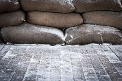 Old brown sandbags on snow covered wooden floor Royalty Free Stock Photography