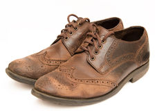 Old brown shoes. Pair of old worn out brown formal brogue shoes. They are isolated on a white background. The shoes have signs of wear and tear, as well as royalty free stock photography