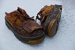 Old brown shoes in the snow in the yard. Old second-hand shoes with a thick sole on the street in the snow Royalty Free Stock Images