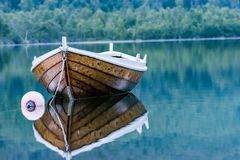 Old brown stylish boat on the water mirror royalty free stock photos