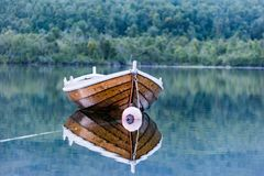 Old brown stylish boat  on the water mirror Royalty Free Stock Photo