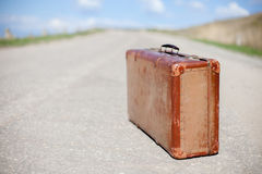 Old brown suitcase stands on a desert road Stock Photo