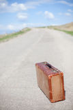 Old brown suitcase stands on a desert road Royalty Free Stock Image
