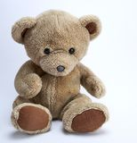 Old brown teddy bear. On a white background stock photography