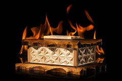 Old brown wooden casket in fire flame on black background Royalty Free Stock Photo