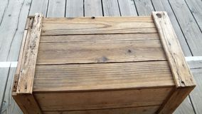 Old brown wooden crate on wooden sidewalk stock photography