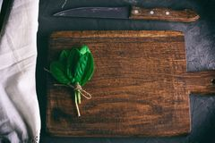 Old brown wooden cutting board with handle and bunch with green. Sorrel leaves, top view, vintage toning royalty free stock image