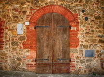 Old brown wooden door in ancient house, Italy. stock images
