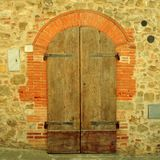 Old brown wooden door in ancient house, Tuscany, Italy. stock image