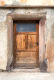 Old brown wooden door with glass insert Royalty Free Stock Photo
