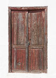 Old brown wooden door in a white facade Stock Image