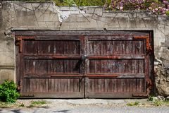 Old brown wooden gate with lock in a stone fence royalty free stock photography