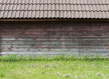 Old brown wooden wall with green grass as background Stock Image