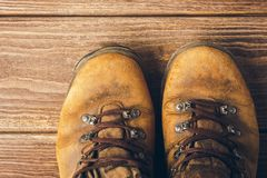 Old brown worn boots close-up on wooden background. Selective focus. Concept of travel and adventure. View from above. royalty free stock photo