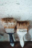 The old Brush near the wall. Old brush on the dirty old wooden table leaning on the wall Stock Photo