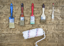 The old brush and roller hanging on a wooden wall. Stock Photo