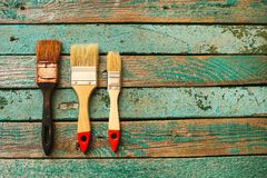 Old brush and two new brushes on a wooden surface. Business concept teamwork, team building. Old brush and two new brushes on a wooden surface. Business concept Stock Image