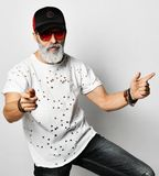 Old brutal man in designer t-shirt, blue jeans and baseball cap pointing a finger and appealing to viewer fashionable men