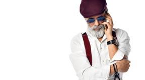 Old brutal senior millionaire man in cap talking on the mobile phone in aviator sunglasses stock photos