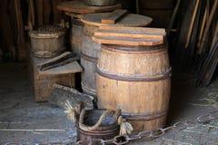 Old buckets and barrels in doorway of rustic barn Stock Image