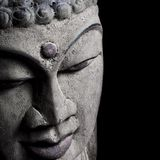 Old Buddha head statue detail on black Stock Images