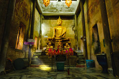 Old Buddha statues in the old church,covered with trees roots with lighting effect. Royalty Free Stock Image