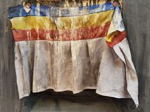 An old Buddhist monastery curtains dirty white with blue, yellow and red stripes hanging on a stone wall. Royalty Free Stock Image