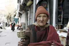 Old buddhist Monk (Lama) rotating prayer wheel on the road in Ladakh, India Royalty Free Stock Photography