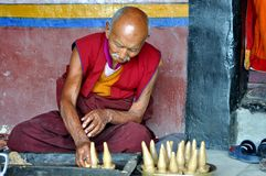 Old Buddhist monk preparing butter sculptures Stock Photos