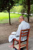 Old buddhist monk reading earnestly Royalty Free Stock Photo