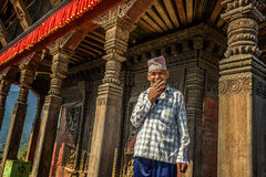 Old buddhist monk smoking cigarette in his temple in Kathmandu Royalty Free Stock Images