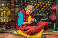 Old buddhist nun sits and begs in Kathmandu, Nepal Royalty Free Stock Photography