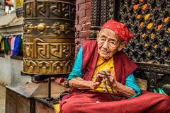 Old buddhist nun sits and begs in Kathmandu, Nepal Stock Photo