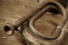 Old bugle, in sepia tone. Old bugle on a rustic wooden table, in sepia tone Royalty Free Stock Images