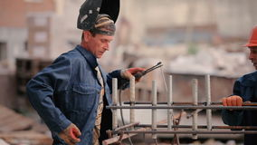 Old builder welding a pipe to the construction. The man measure the distance between the pipes. The man put the helmet at the face and start welding the pipe stock video