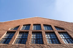 Old building. Old red brick building over blue sky.Old building and plants Stock Images